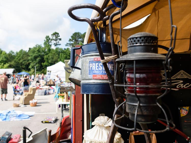A lantern hangs on a tent booth at a yard sale event