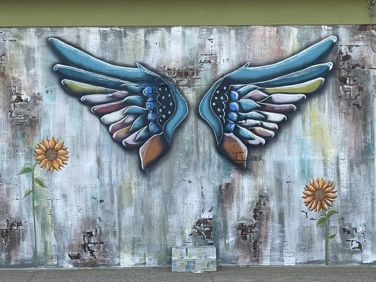 Blue wings painted on a wall with a space in the middle to stand