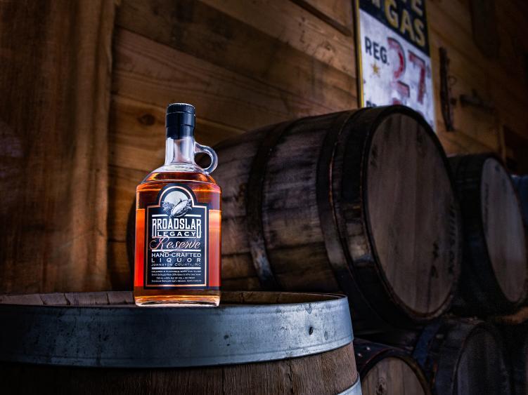 Broadslab Legacy Shine Bottle sitting on a barrel