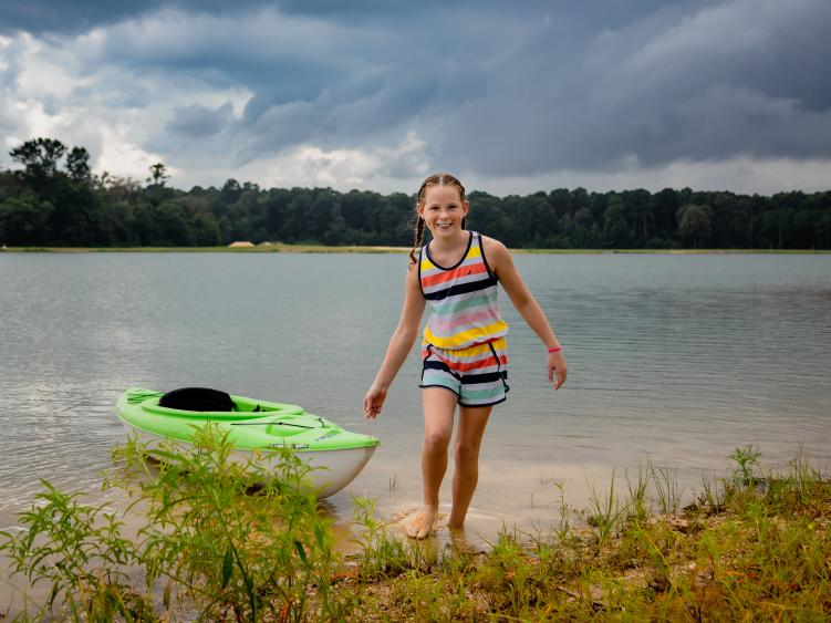A little girl pulls a kayak out of the lake while smiling at the camera