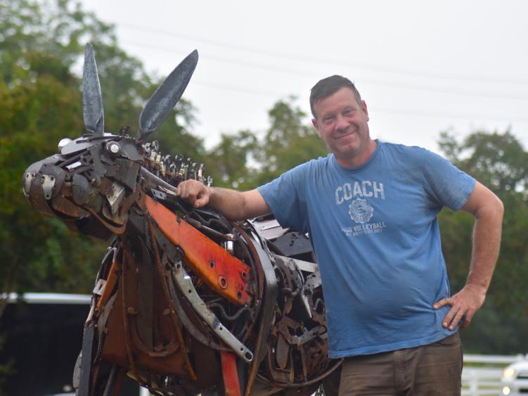 Artist Jonathan Bowling stands with Benson Mule Sculpture