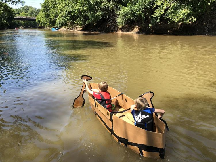 Two Kids Paddle a Cardboard Boat Along The Neuse River