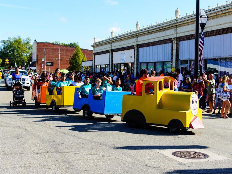 A small train carrying passengers down the streets of Selma, NC, for the annual Selma Railroad Days.