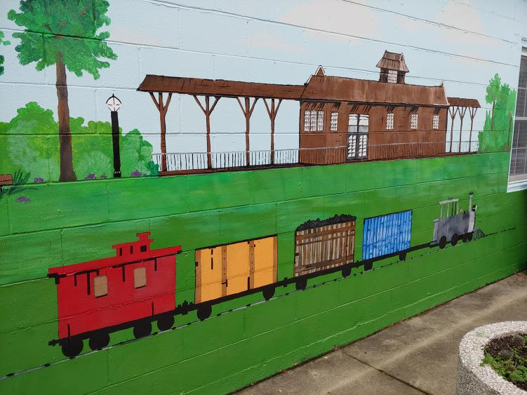 A mural of a train in front of a train station in Selma's Vick Park