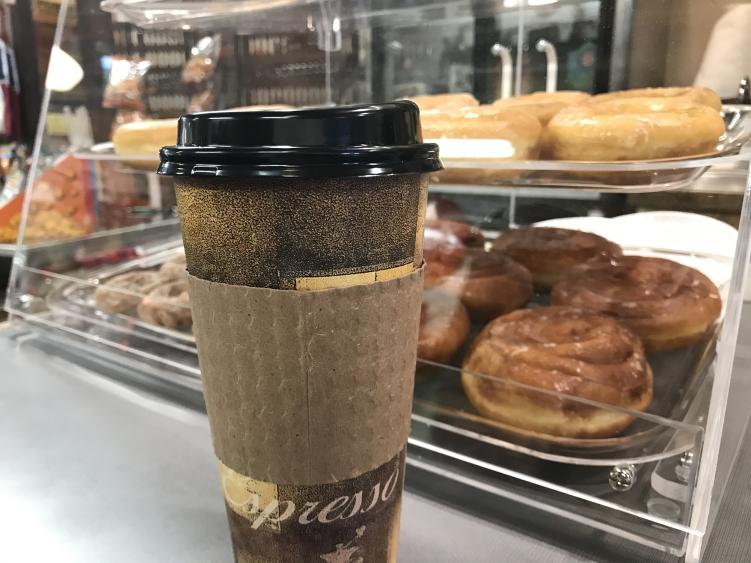 A to-go coffee cup sits in front of a baked goods case