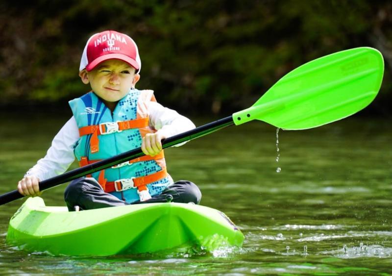 A little boy kayaking on Griffy Lake