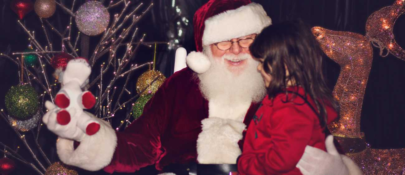 a little girl sits on Santa's lap