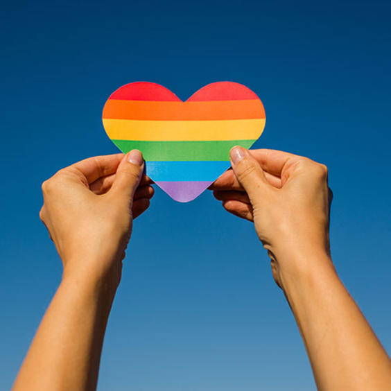 two hands holding a heart made of rainbow colors