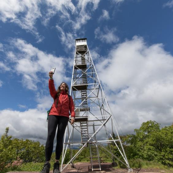 Woman taking a selfie in front of a fire tower