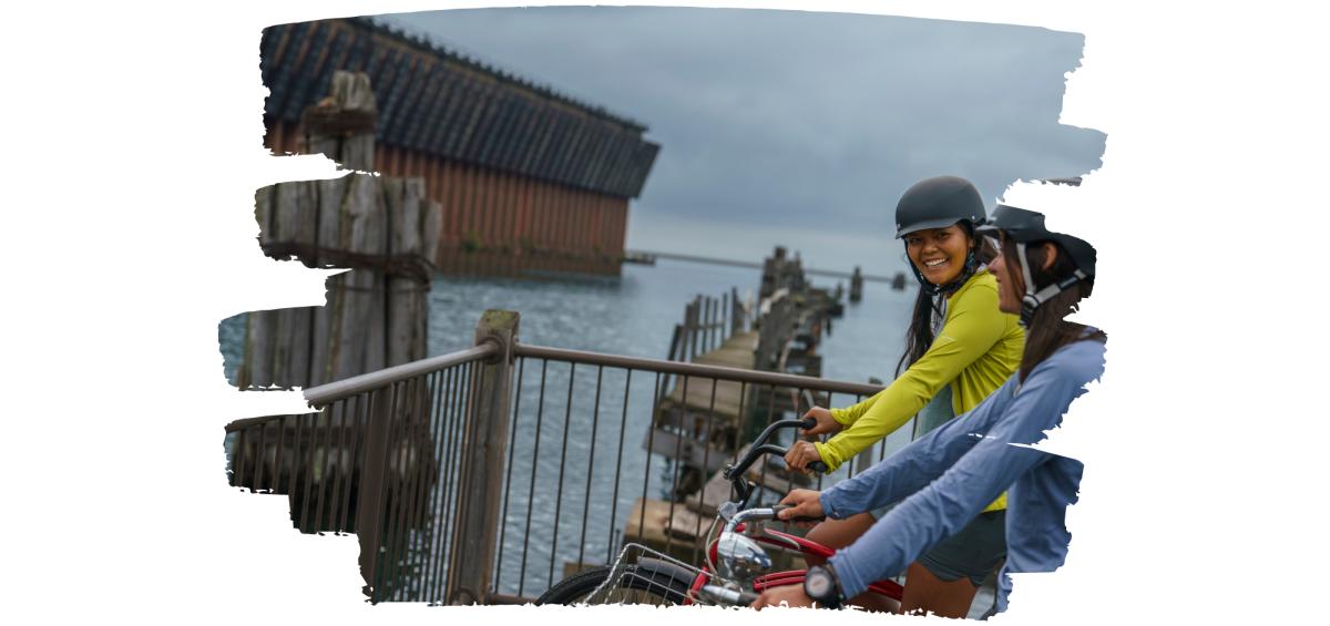 Two women admiring the Lower Harbor Ore Dock on bike.