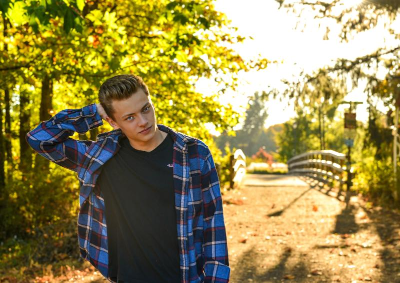 Person in flannel shirt stands in front of a sun-soaked footbridge among fall foliage.
