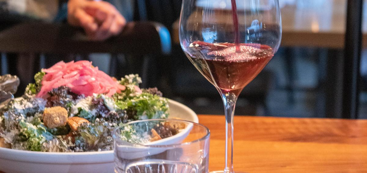 A glass of wine and bowl of salad at Kindred Fare.