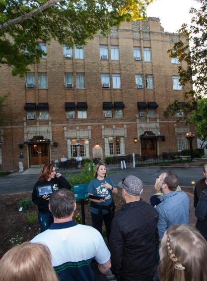 A small group stands in front of the haunted Faust Hotel on a ghost tour in New Braunfels, Texas.