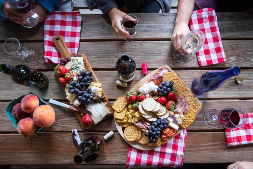 A overhead photo of a picnic with wine and cheese