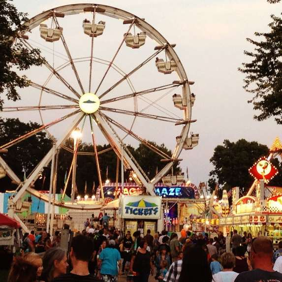 Crowd by food vendors and ferris wheel at the Monroe County Fair