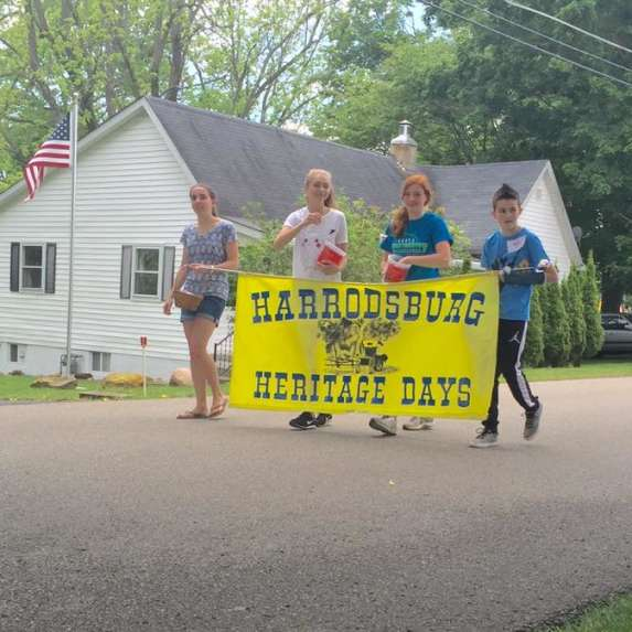 Four kids holding the Heritage Days sign ahead of the festival's parade