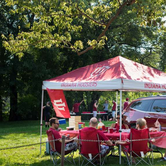 People tailgating under a canopy
