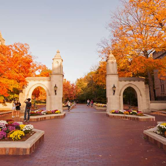 The Sample Gates at Indiana University with the surrounding trees changing color in fall