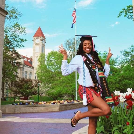 IU Graduate posing at Sample Gates