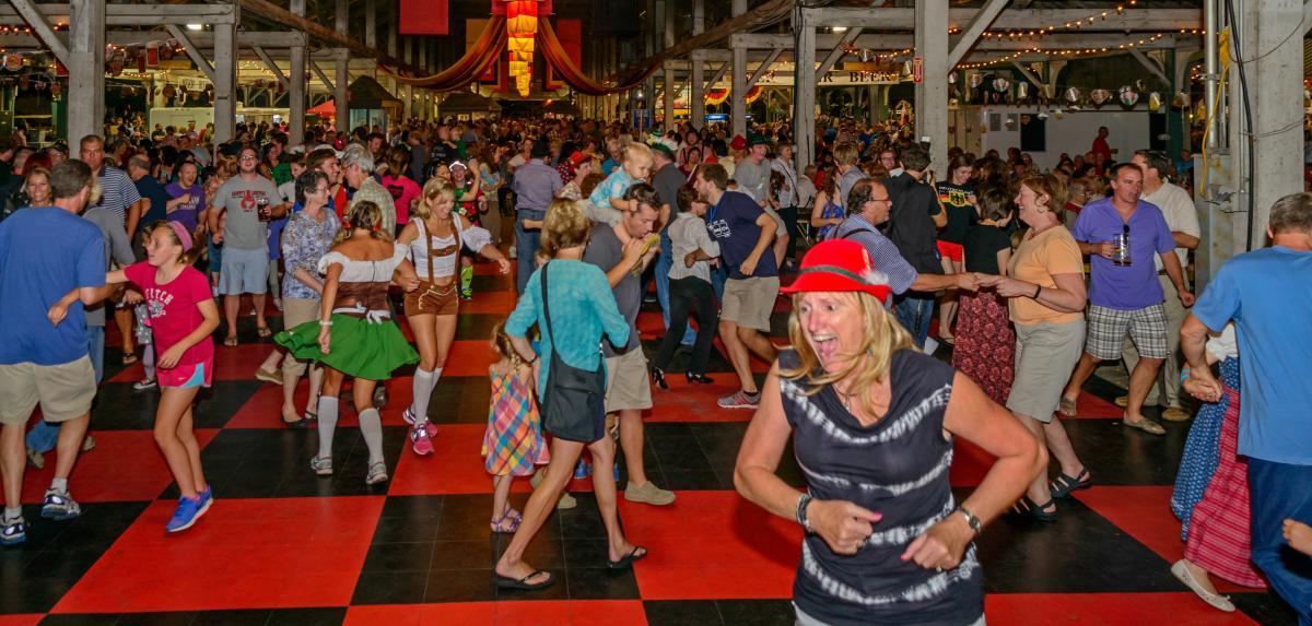 Dancing crowd in leiderhosen and traditional German hats at Columbus Oktoberfest