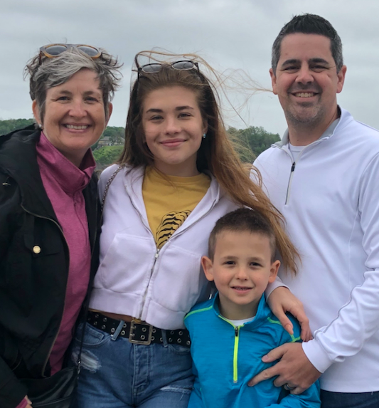 Julie Kirkpatrick, CEO of meetNKY, smiling at the camera with her family