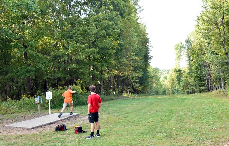 father and son playing disc golf