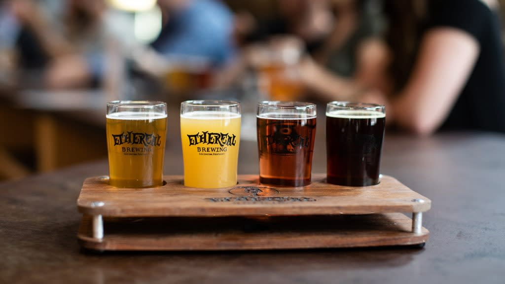 A flight of four beers from Ethereal Brewing in a wooden holder.