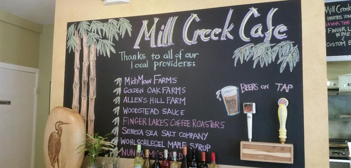 Chalkboard sign inside Mill Creek Cafe thanking local providers, including: MichMaw Farms, Golden Oak Farms, Allen's Hill Farm, Woodstead Sauce, Finger Lakes Coffee Roasters, Seneca Sea Salt Company, and Wolhschlegel Maple Syrup. Beers on tap are also advertised.