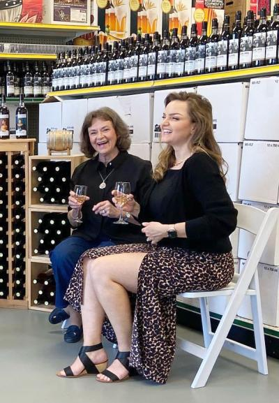 Ava Thompson and Ava Malissa Silver sitting in white chairs, smiling and laughing while holding wine glasses at Seven Jars Wine Launch event.