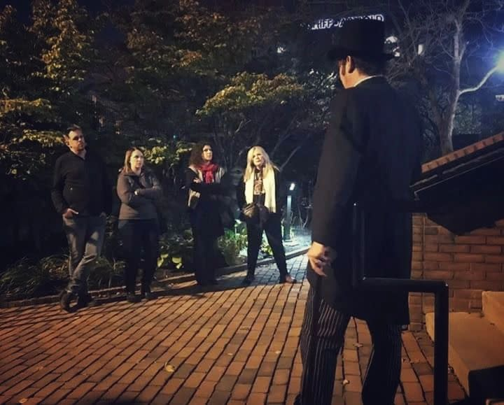 A Group Of People Listening To A Tour Guide At Columbus Ghost Tours during Halloween