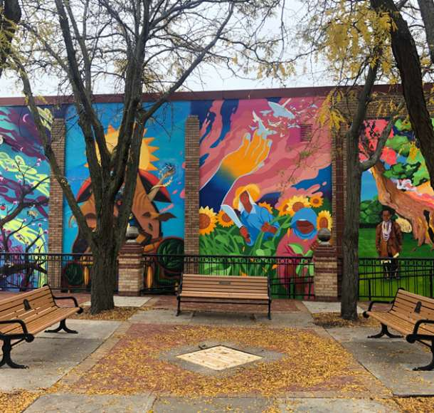 Benches and trees in front of four mural segments in Overland Park