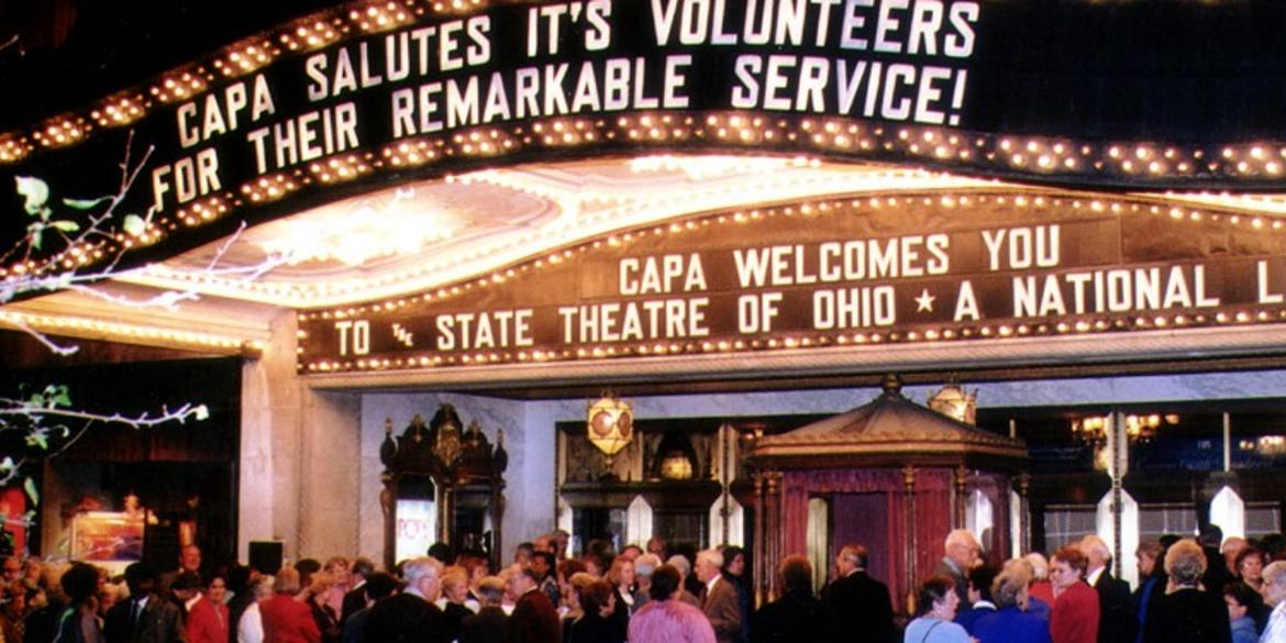 Crowd of people outside the doors and under bright, lit-up signs of the Ohio Theatre
