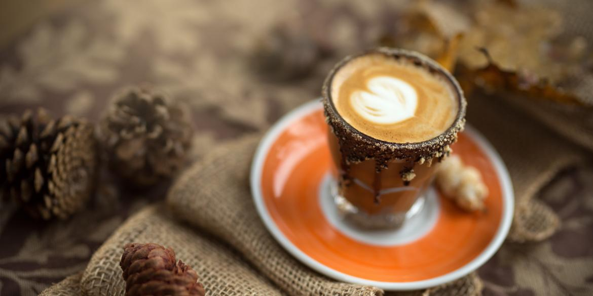 Fall-themed coffee with chocolate drizzle and foam on orange dish surrounded by burlap and pine cones