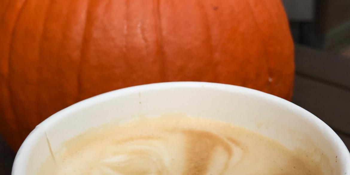 Close-up of pumpkin coffee with foam standing in front of pumpkin