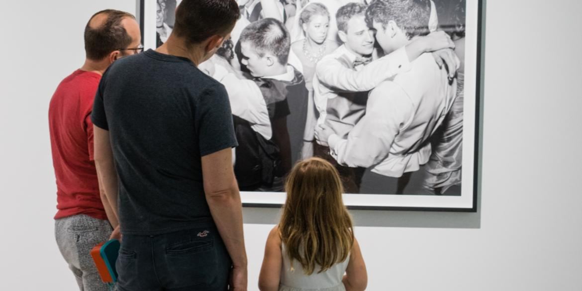 View from behind of two men and young girl viewing art photograph on wall in Pizzuti Collection
