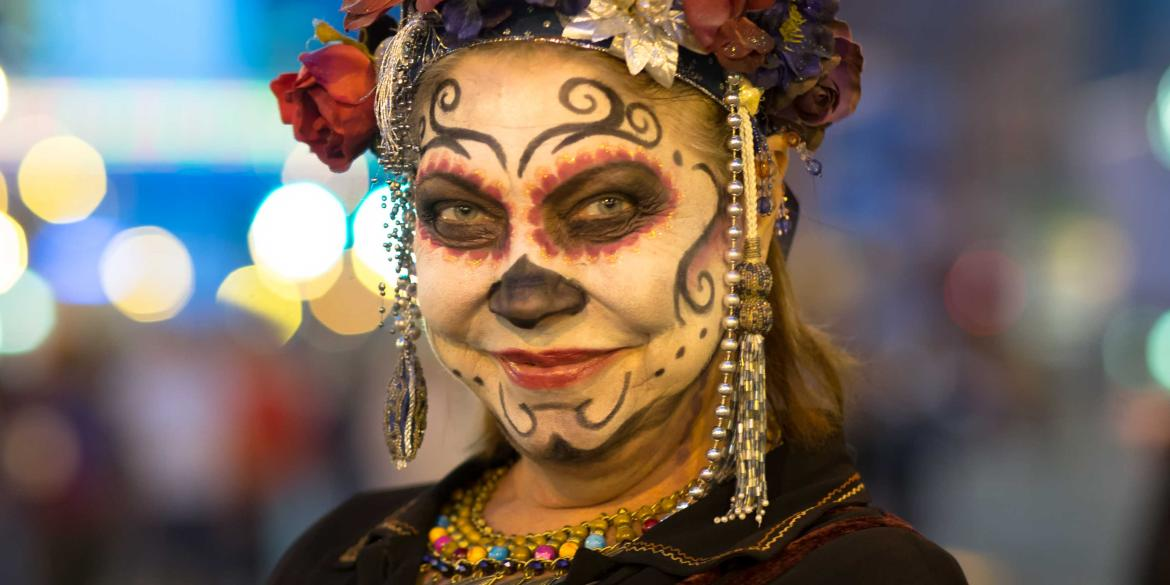 A woman has her face painted for Dia de los Muertos during Highball Halloween