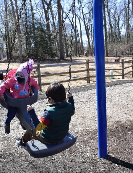 Two children play on a swing at Lake Waterford
