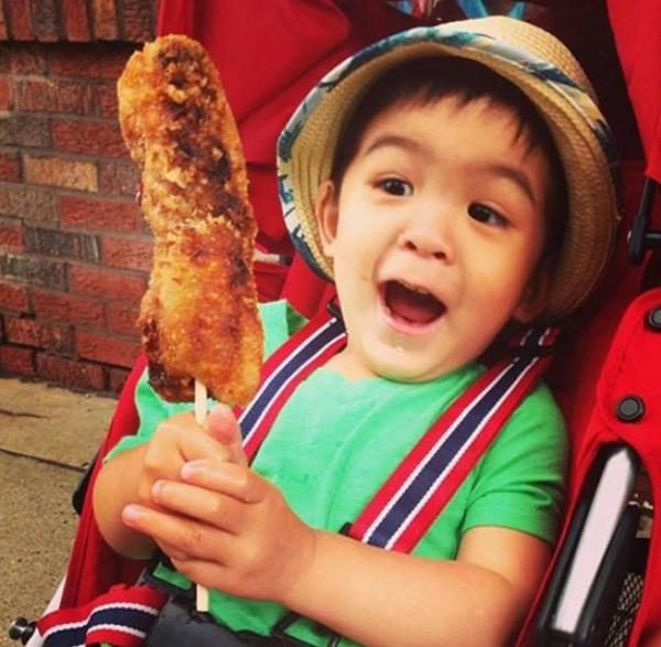 Child holding a giant egg roll on a stick