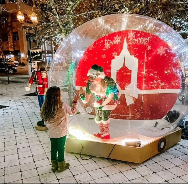 Elf inside a Snow Globe touching hands through the glass with a little girl in Town Center