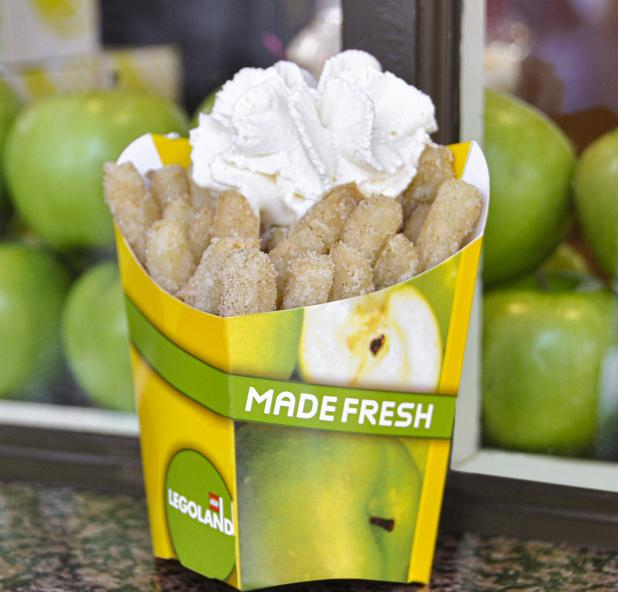"""A box of apple fries topped with whipped cream in a box that reads """"made fresh"""""""