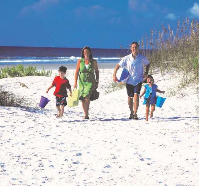 Family walking thru dunes at Wrightsville Beach