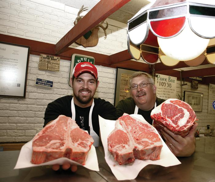 2 Men showing off cuts of beef at Meads Longwood Meat Market In Rockford, IL