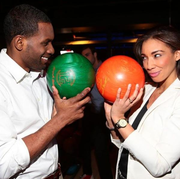 A man and woman hold bowling balls and stare at each other as they prepare for a competitive game of bowling