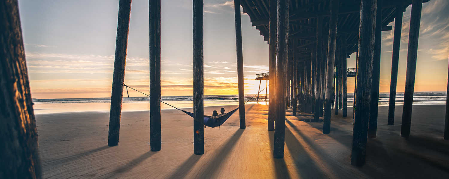 A couple relaxes in a hammock strung between pier pylons on a SLO CAL beach at sunset.
