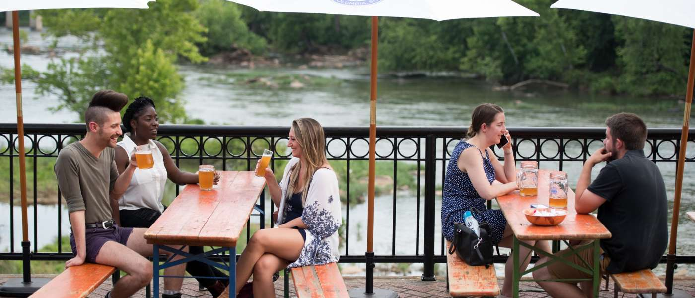 People drinking beer by a river