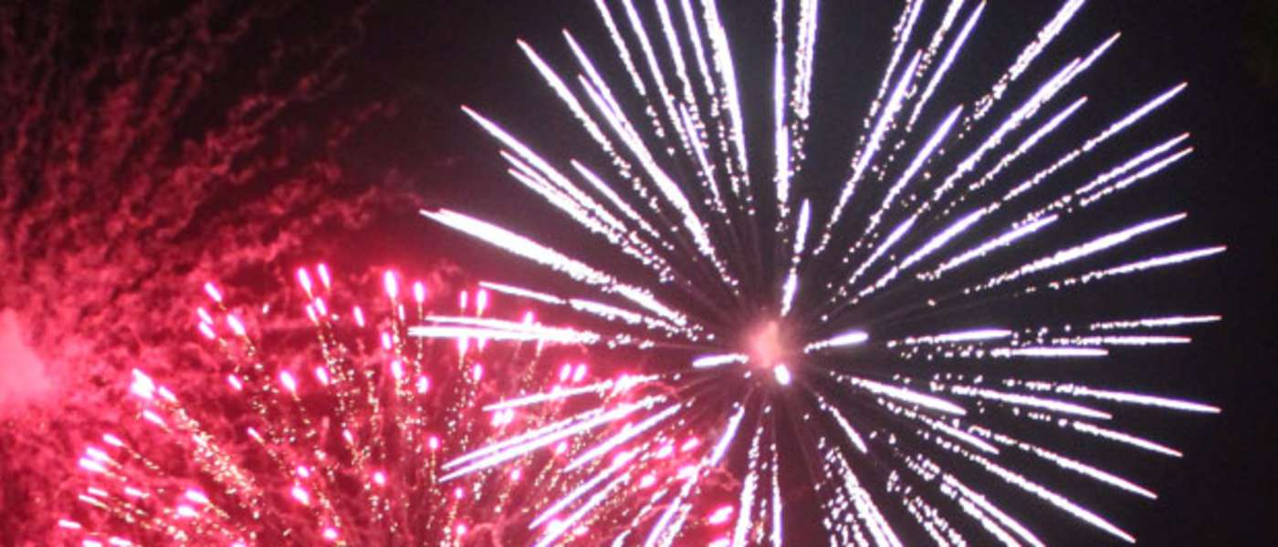 Red and white firework burst in night sky