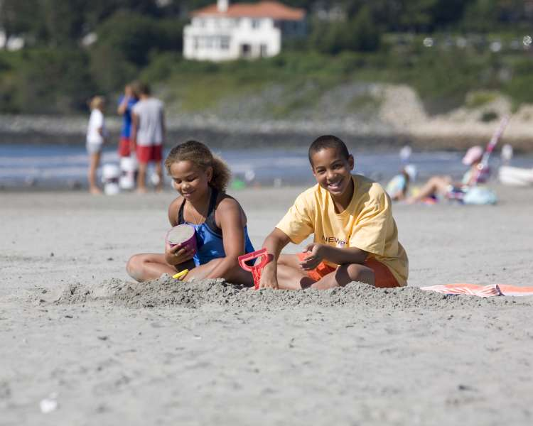 Two children playing in the sand at the beach.