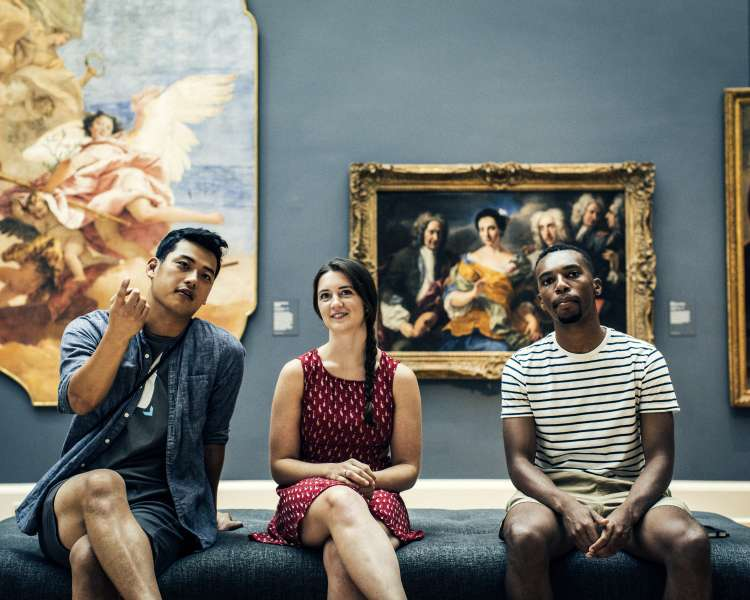 Three young adults explore the RISD Museum.