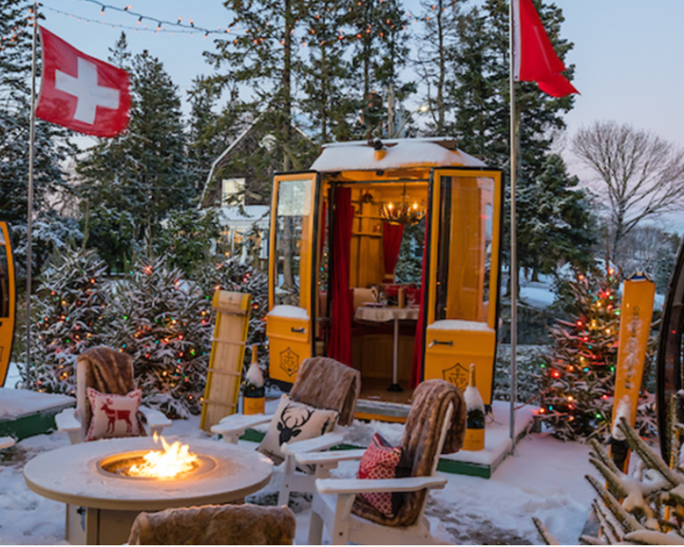 A swiss chalet in the snow with flags and fire pit.