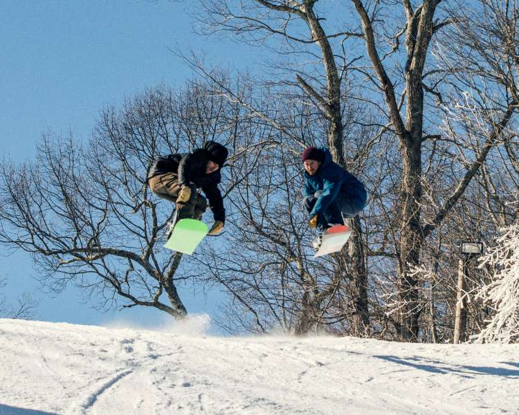 Two snowboarders catching air at Yawgoo Valley Ski Area in Exeter, RI
